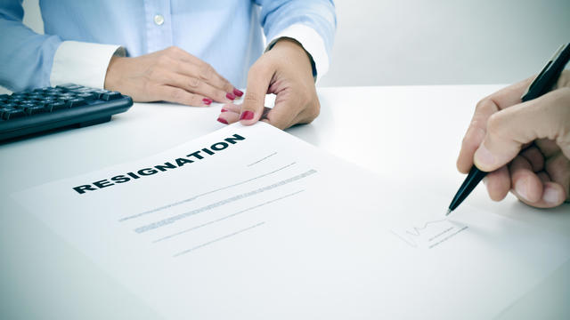 man signing a resignation document