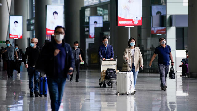 FILE PHOTO: People wearing face masks are seen at Hongqiao International Airport in Shanghai