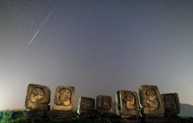 A meteor streaks past stars in the night sky above the Necropolis on Smrike for the victims of Fascism during the Perseid meteor shower in Novi Travnik