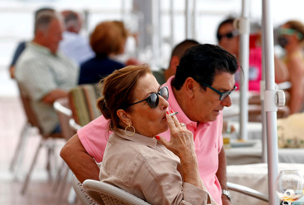 A woman smokes at the terrace of a restaurant, during the spread of the coronavirus disease (COVID-19) pandemic, in Las Palmas