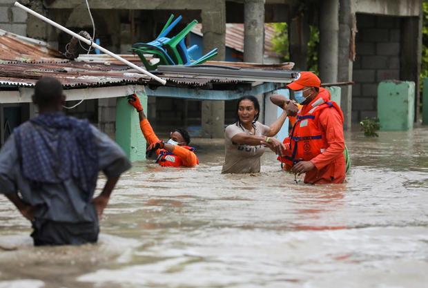 Members of the Civil Defence help a woman in a flooded street after the passage of Storm Laura, in Azua