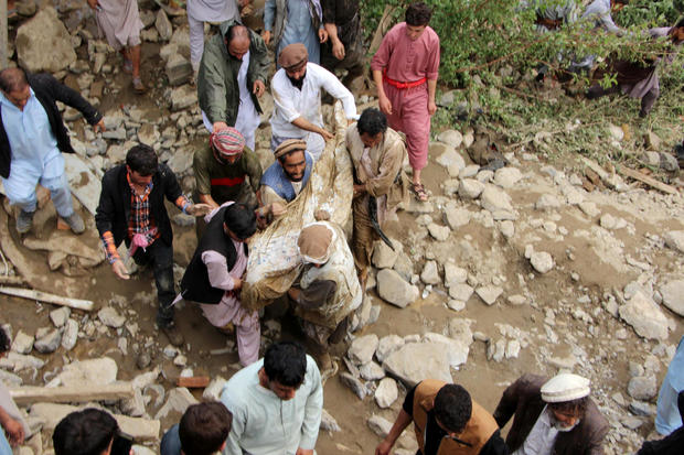 Men carry a victim who died in the floods in Charikar