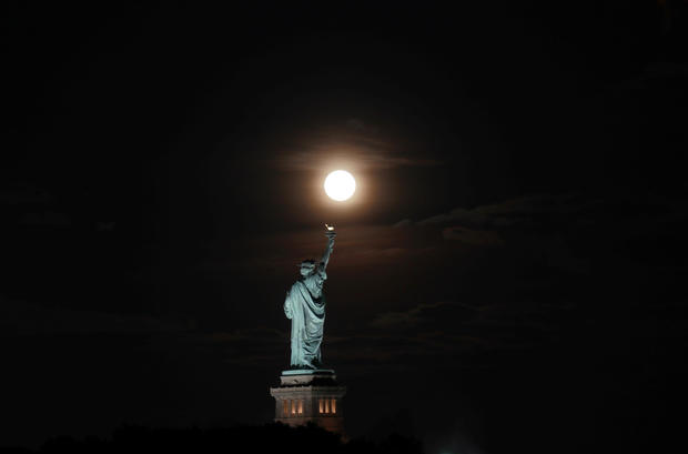india The Harvest Moon Rises Behind the Statue of Liberty in New York City