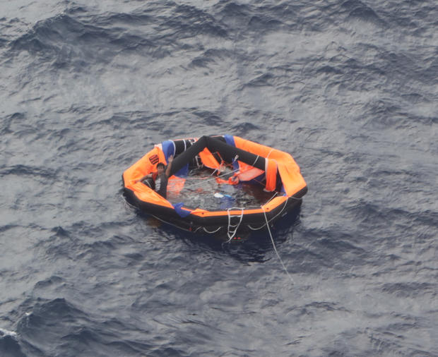 An aerial view taken from an airplane of Japan Coast Guard shows a Filipino crew member of the Gulf Livestock 1 on a life raft in the East China Sea