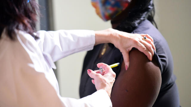 nurse giving a woman a vaccine injection.jpg