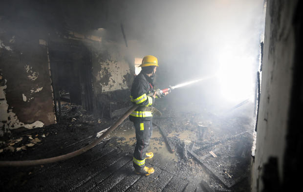 A firefighters extinguishes a fire in a house caused by shelling in the fighting over the breakaway region of Nagorno-Karabakh in the town of Barda