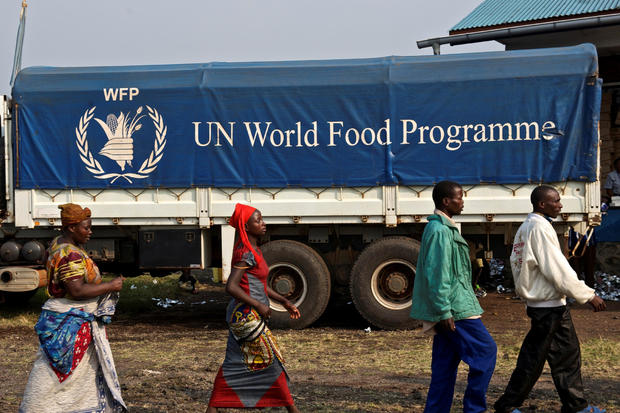 FILE PHOTO: Displaced Congolese civilians walk past a truck carrying food for distribution at Kibati, just outside the eastern Congolese city of Goma