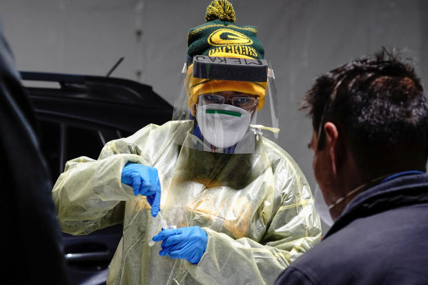 Certified nursing assistant Shameka Johnson, wearing Green Bay Packers apparel, processes a nasal swab at a drive-thru testing site outside the Southside Health Center as the coronavirus disease outbreak continues in Milwaukee, Wisconsin, October 21, 2020