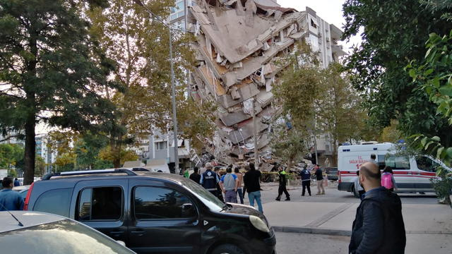 Locals look at a damaged building in Izmir