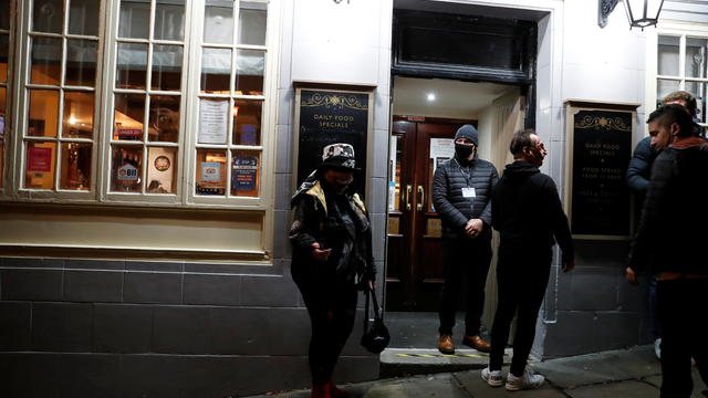 People stand outside a pub after Britain's Prime Minister Boris Johnson announced on TV a second national lockdown, in Durham