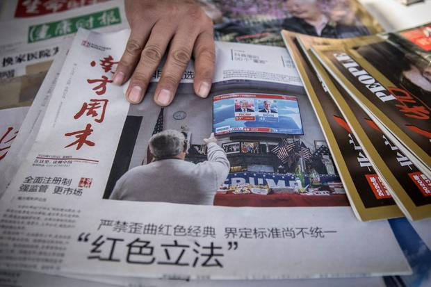 The front page of the Southern Weekly newspaper shows a picture of U.S. President Donald Trump and President-elect Joe Biden at a news stand in Beijing