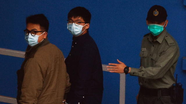 Pro-democracy activists Ivan Lam and Joshua Wong arrive at Lai Chi Kok Reception Centre by prison van after pleading guilty to charges of organising and inciting an unauthorised assembly near the police headquarters during last year's anti-government prot