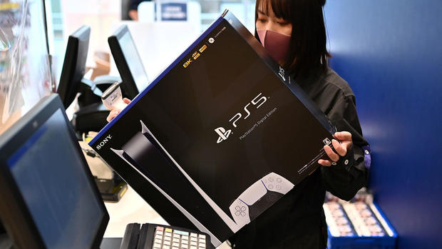 Masked cashier ringing up a Sony PlayStation 5