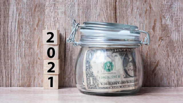 2021 Happy New Year with US dollar money glass American on wood table background. business, investment, retirement planning, finance, Saving and New Year Resolution concepts