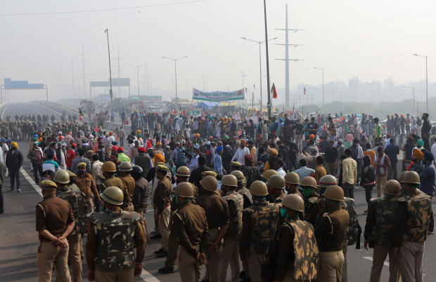 Security officers look on as farmers block the highway