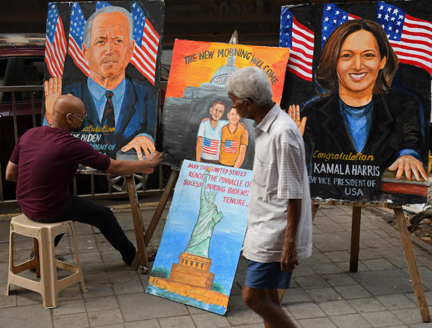 A man walks past an artist painting portraits of Joe Biden and Kamala Harris