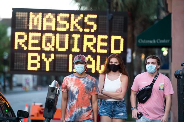 People wearing protective face masks walk along King Street on July 18, 2020, in Charleston, South Carolina.