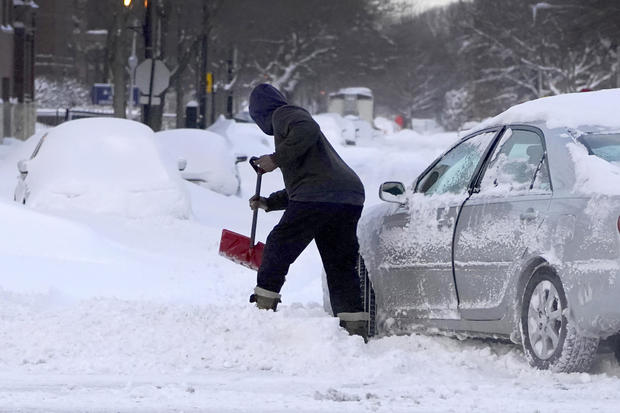 A motorist digs a path for his car February 16, 2021, to enter an unplowed side street in the Bronzeville neighborhood of the South Side of Chicago.