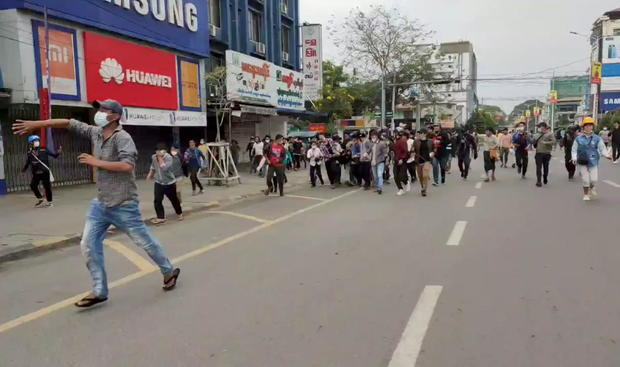 People evacuate an injured demonstrator during a protest in Myitkyina