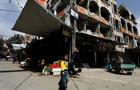 A boy walks past shops in Douma