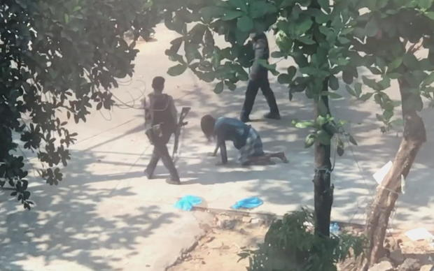Police officer carrying a rifle forces a man to crawl on all fours in Yangon