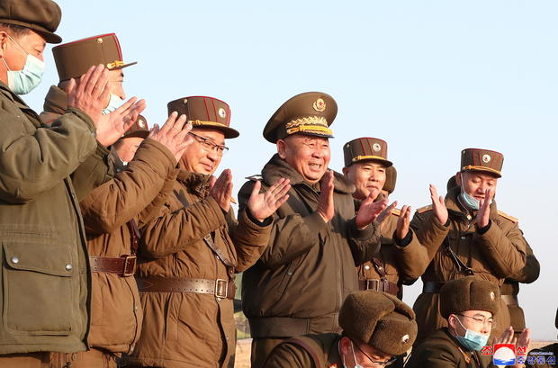 Ri Pyong Chol, the senior leader who is overseeing the test, and other military officials applaud after the launch of a newly developed new-type tactical guided projectile
