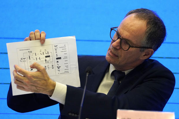 Peter Ben Embarek of the World Health Organization holds up a chart showing pathways of transmission of the coronavirus during a joint news conference at the end of a mission in Wuhan in central China's Hubei province February 9, 2021.