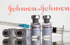 """FILE PHOTO: FILE PHOTO: Vials labelled """"COVID-19 Coronavirus Vaccine"""" and sryinge are seen in front of displayed J&J logo in this illustration"""