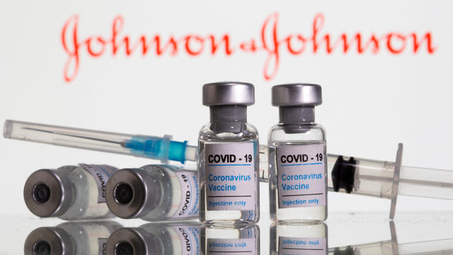 "FILE PHOTO: FILE PHOTO: Vials labelled ""COVID-19 Coronavirus Vaccine"" and sryinge are seen in front of displayed J&J logo in this illustration"