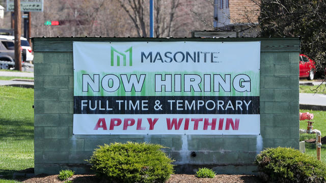 A now hiring sign is seen outside of Masonite, a door and
