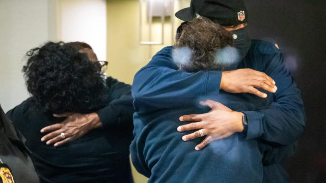 People embrace after learning their loved one was safe after a mass shooting at the FedEx facility in Indianapolis, Indiana, April 16, 2021.