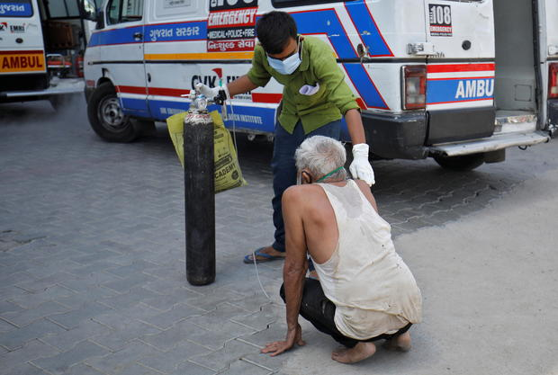 A patient with breathing problem is helped by his relative to enter a COVID-19 hospital for treatment, in Ahmedabad