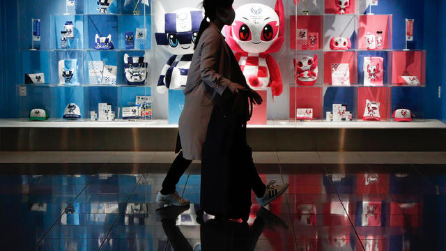 A shopper walks past the official shop of the Tokyo Olympics