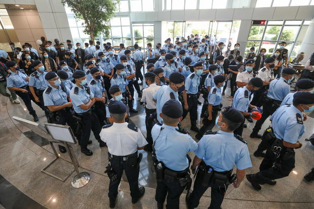 Police officers gather at the headquarters of Apple Daily in Hong Kong