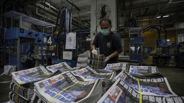 An employee stacks freshly printed papers onto a pallet in