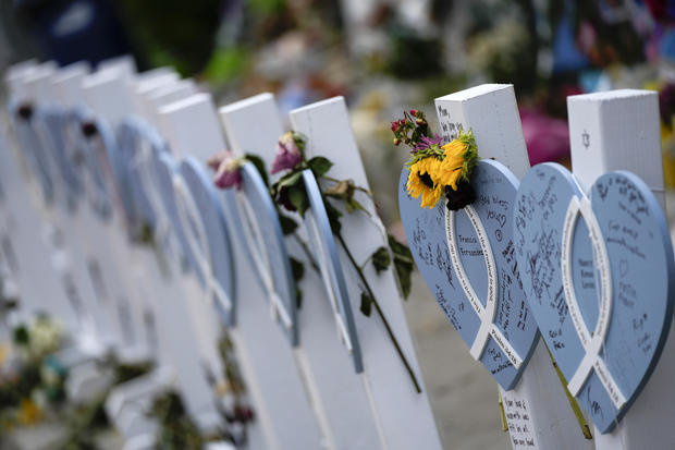 Flowers and messages of love adorn wooden hearts with the names of victims of the Champlain Towers South building collapse, at a makeshift memorial near the site July 12, 2021, in Surfside, Florida.
