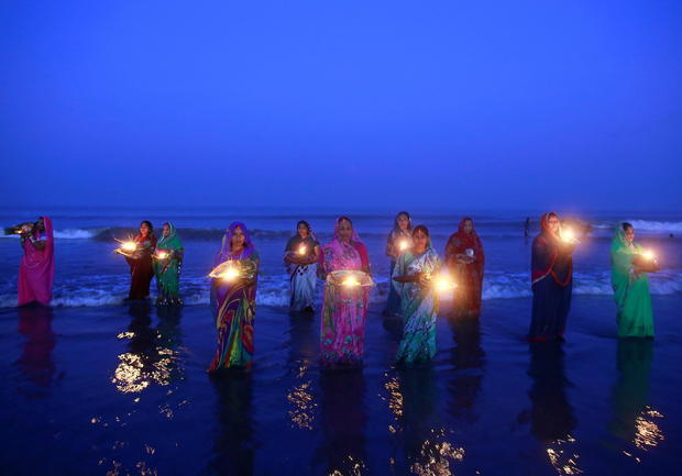 """FILE PHOTO: Hindu devotees pray while standing in the waters of the Arabian Sea as they worship the Sun god Surya during the Hindu religious festival """"Chatt Puja"""" in Mumbai"""