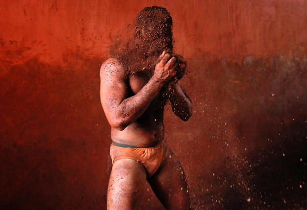 FILE PHOTO: A wrestler rubs his hands with mud to prevent slipping due to sweat, during a traditional mud wrestling bout in Kolhapur