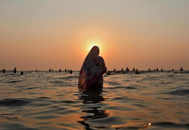 FILE PHOTO: Hindu devotees worship the Sun god in the waters of the Arabian Sea during Chhath Puja in Mumbai