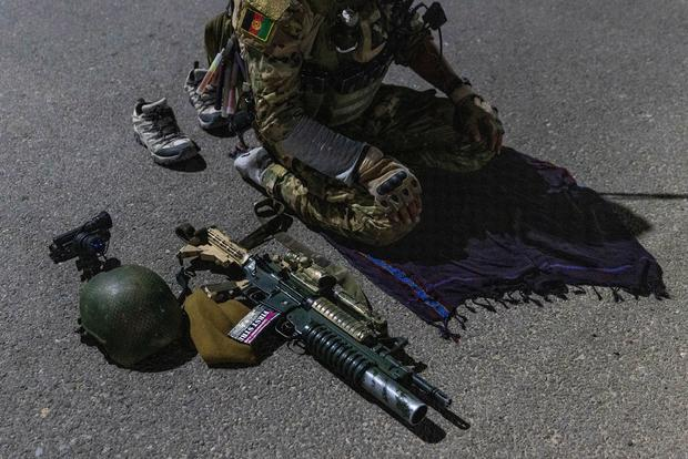 A member of the Afghan Special Forces prays on a highway before a combat mission against Taliban, in Kandahar province