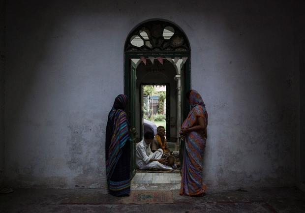 FILE PHOTO: Relatives of patrons listen to priests as they chant during evening prayers at the Mukti Bhavan in Varanasi
