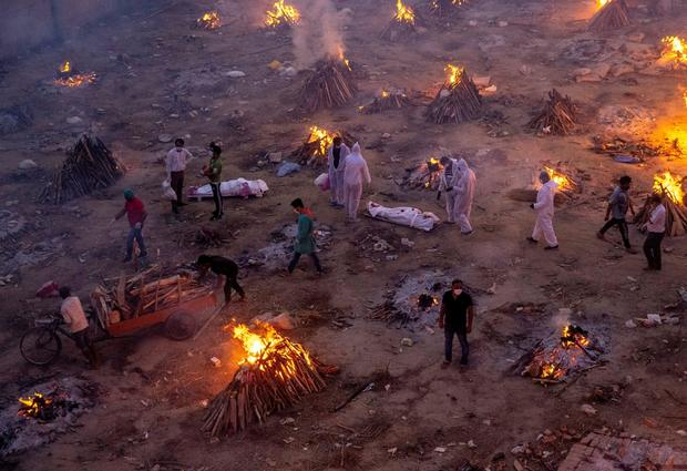 FILE PHOTO: People wait to cremate COVID-19 victims at a crematorium ground in New Delhi