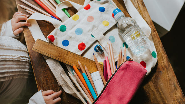 Child looking at a Spotty Schoolbag with Stationary Surrounding
