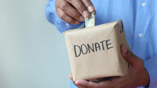 Donating For Corona Virus. Man Puts Donation In A Box With Copy Space