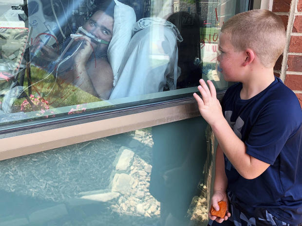 Six-year-old Brody Barker waves to his father, Daryl, from outside his hospital room July 26, 2021, in Osage Beach, Missouri, where Daryl has been hospitalized for nearly three weeks for COVID. Daryl told reporters he had resisted getting vaccinated.