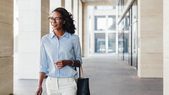 Female business professional walking outside an office building with bag on a hand
