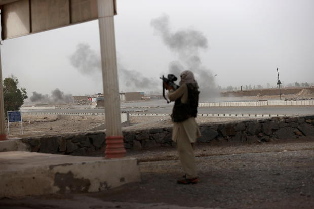 An Afghan soldier holds a gun and looks towards Taliban positions as smoke rises in the distance from clashes on the outskirts of Spin Boldak in Kandahar province, Afghanistan