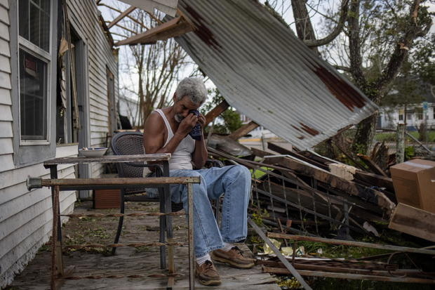 Man weeps on porch of home damaged by Hurricane Ida in Louisiana