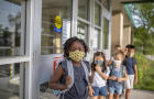 Diverse group of elementary school kids go back to school wearing masks
