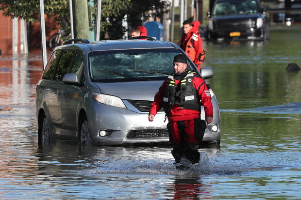 A first responder wades through floodwaters after the remnants of Ida brought drenching rain, flash floods and tornadoes to parts of the Northeast, in Mamaroneck, New York, September 2, 2021.